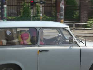 An Ostalgie trifecta: A Trabant stuffed with East German plushes, with the Sandmännchen riding beside the driver, and an Ampelmännchen in the background